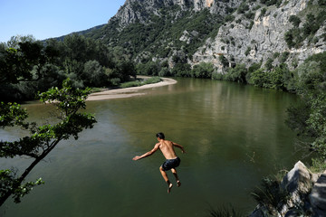 A boy jumps into the river of Nestos in Galani village near the city of Xanthi,