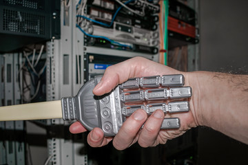 Handshake of man and robot. The concept of friendship between man and machine. The hand of the person and the robot on the background of the servent room of the data center