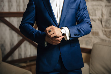 A close-up of a cropped frame of a man puts on a gold watch with a leather belt, is dressed in a stylish suit, a white shirt, wears a gold ring.