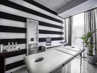 View of an Interior of a modern clean massage room with black and white luxury decor.