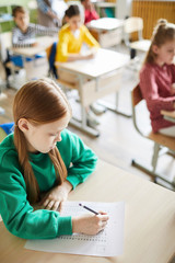 Serious concentrated cute girl in green sweater filling quiz blank while solving task at lesson in school