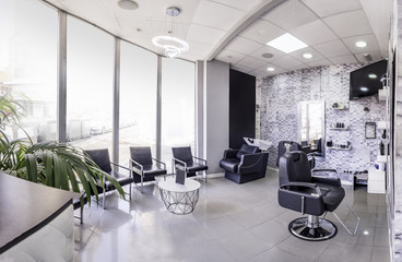 Panorama of a  modern bright beauty salon. Hair salon interior business with black and white luxury decor.