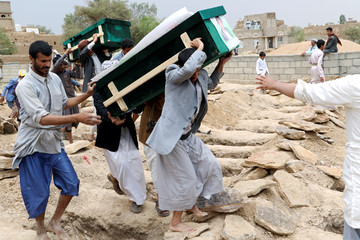 Mourners carry coffins during a funeral of people, mainly children, killed in a Saudi-led coalition air strike on a bus in northern Yemen, in Saada