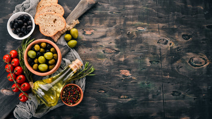 A set of olives, olive oil, bread, cheese and spices. On a black wooden background. Free space for text.