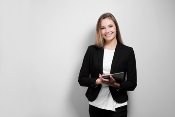 Portrait of a beautiful smiling woman blonde with a tablet in her hands in a business suit and jacket on a white background. A student or a businesswoman is working.