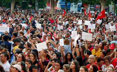 Protesters shout slogans and hold national flags during a rally, demanding equal inheritance rights for women, in Tunis