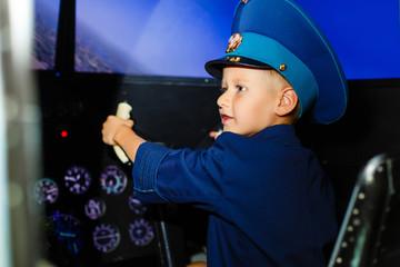 A happy, kindergarten boy toting in an oversized airline pilot uniform