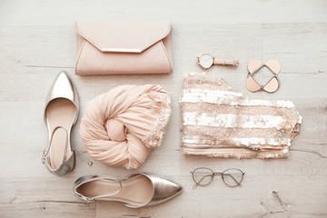 Flat lay composition with stylish outfit for woman on wooden background