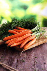 Fresh organic carrots with green leaves on wooden background. Ve