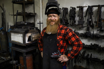 Cheerful satisfied handsome welder in mask on head and apron smiling at camera and holding hands on hips in workshop with various tools hanging on wall.