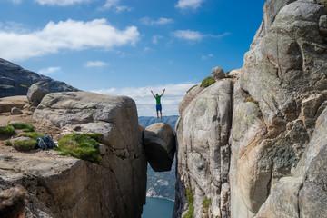 Man jumping over Kjeragbolten in Norway. Kjerag