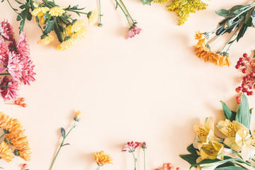 Autumn composition. Frame made of fresh flowers on pastel beige background. Autumn, fall concept....