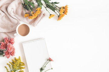 Autumn composition. Cup of coffee, notepad, fresh flowers on white background. Autumn, fall concept. Flat lay, top view, copy space
