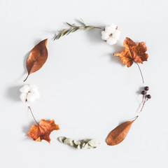 Autumn composition. Wreath made of eucalyptus branches, cotton flowers, dried leaves on pastel gray background. Autumn, fall concept. Flat lay, top view, copy space, square