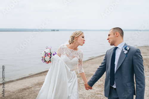 eb9fed02879835 A beautiful bride in a lace dress and a stylish bridegroom stroll and walk  on the pier