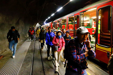 Tourists leave a train after arriving at Jungfraujoch station at the Jungfraujoch