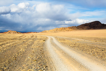 Landscape of a road through the steppe and mountains in Western Mongolia.