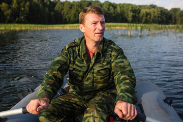 Man fisherman in camouflage on a rubber boat floating in the lake.