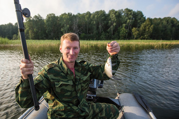Fisherman in camouflage on a rubber boat in the lake.