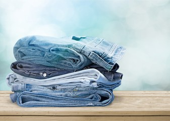 Pile of blue jeans over white background