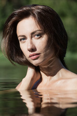 Young brunette woman natural portrait outdoors in water, shallow depth of field