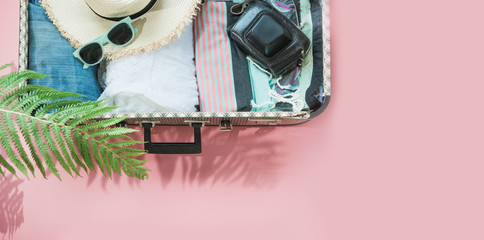Open suitcase with female clothes for trip on pastel pink. Top view with copy space. Summer concept travel.
