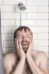 A handsome, bearded man stands in the shower under running warm water, holding his hands on his face and smiling happily.