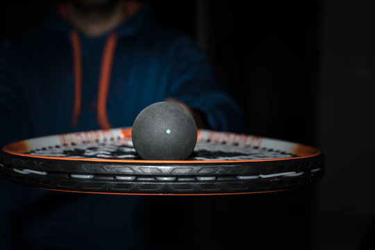 Single dot squash ball on the strings of a racquet