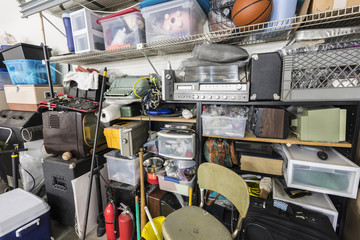 Full shelves of vintage electronics, boxes and sports equipment in typical suburban garage.