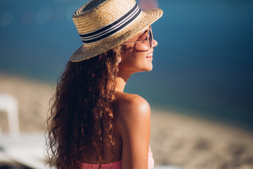 Laughing freedom woman,Cool hipster girl in summer straw hat posing beside summer beach hot summer fashion accessory,stylish sunglasses,bikini.Sexy perfect fit body woman. Copy, empty space for text