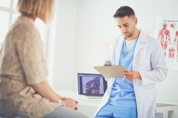 Handsome doctor is talking with young female patient and making notes while sitting in his office