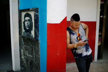 "A young Cuban checks his phone at an internet hotspot next to a picture of late revolutionary hero Ernesto ""Che"" Guevara in Havana"