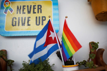 A Cuban flag and a Pride rainbow flag symbolising gay rights are seen at the balcony of the apartment of same-sex couple Mercedes Garcia and Onelia Miranda in Havana