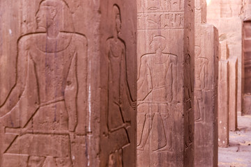 Stone Columns wall with Egyptian carving figures and hieroglyphs, Aswan, Egypt, Africa.