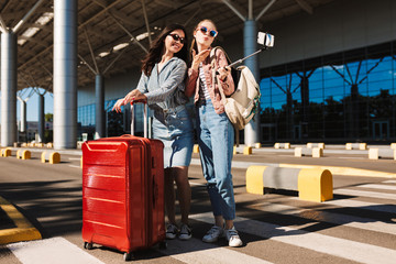 Pretty girls in sunglasses happily sending air kisses while taking photos on cellphone together with red suitcase and backpack on shoulder outdoor near airport