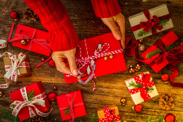 Christmas gift giving - hands wrapping red and white paper christmas gift boxes with decorations on wooden background, retro toned