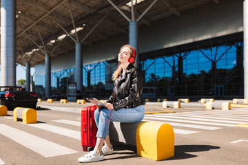 Pretty girl in headphones dreamily closing eyes holding the tablet in hands and red suitcase near with airport on background