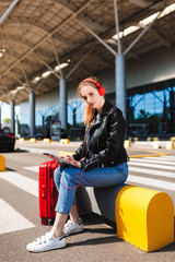 Beautiful girl in headphones dreamily looking in camera holding the tablet in hands and suitcase near with airport on background