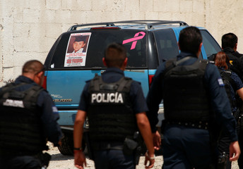 Police officers walk in front of a car showing a picture of 6-year-old David Rafael Santillan in Ciudad Juarez