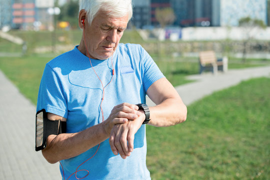 Waist up portrait of modern senior man setting up smart watch and listening to music while doing morning run in park, copy space