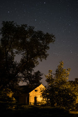 house in rural landscape at night with starlit sky -