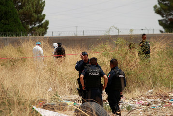 Members of a forensic team work in an empty lot where the body of 6-year-old David Rafael Santillan, who according to local media disappeared on August 8 and was found dead on August 13 close to his house, in Ciudad Juarez