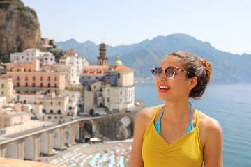 Portrait of young smiling woman with sunglasses in Atrani village, Amalfi Coast, Italy. Picture of female tourist in her summer holidays in Southern Italy.