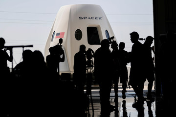 Members of the media gather around a replica of the Crew Dragon spacecraft at SpaceX headquarters in Hawthorne, California