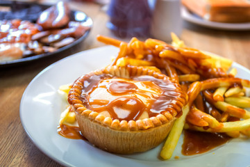 A plate of mince beef pie served with potato chips in traditional English meal