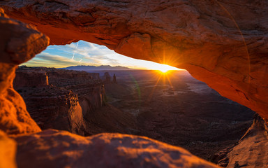Deurstickers Bruin Cliff's-edge sandstone Mesa Arch framing an iconic sunrise view of the red rock canyon landscape below.