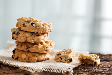 Pile of chocolate chip cookies on wooden desk.