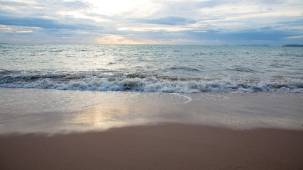 Sand beach with sea waves in the sunset.