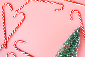 Top view of Christmas tree with many candy cane on pastel pink  background.Holiday festive celebration greeting card with copy space to addng text.