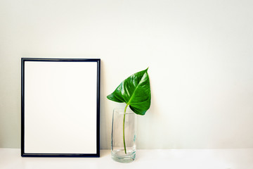 Black photo frame and green plant in a chrystal vase arranged against emty grey wall. Frame mock-up.
